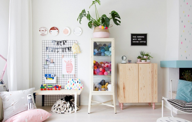 A glass cabinet is filled with toys and there's a desk for kids