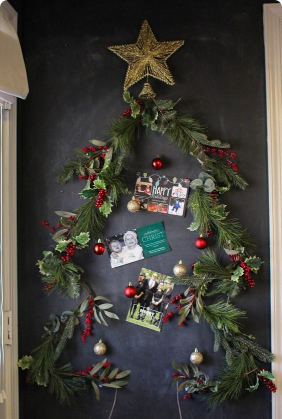 Christmas garland attached to a chalkboard as a tree and cards inside it
