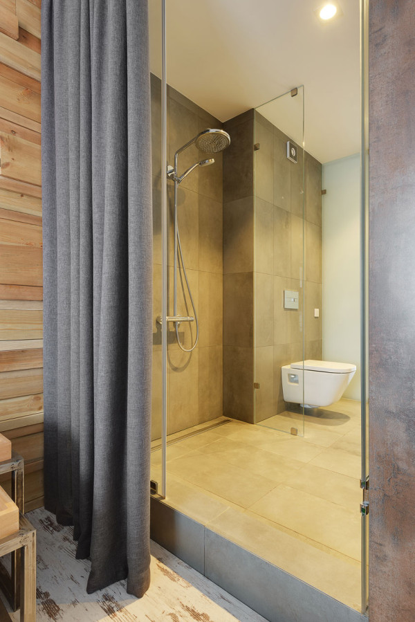 The bathroom has a walk-in shower and is hidden with a curtain from the bedroom to keep it more private