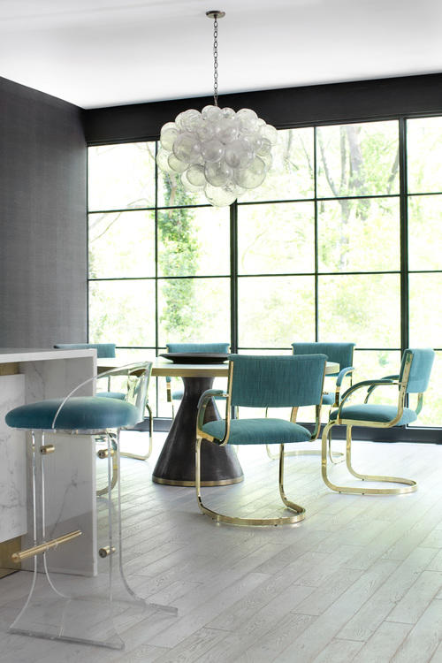 The dining area is located by the window, and the upholstered gilded chairs echo with the lucite ones