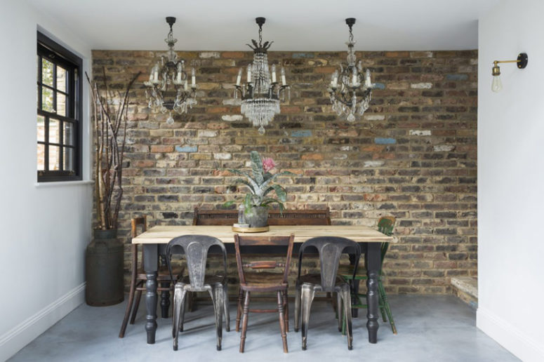 The dining space is vintage and industrial, with a rustic table, vintage chandeliers and industrial chairs