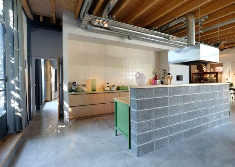 The kitchen has pure white tiles, exposed pipes and a unique concrete countertop imitating brick clad