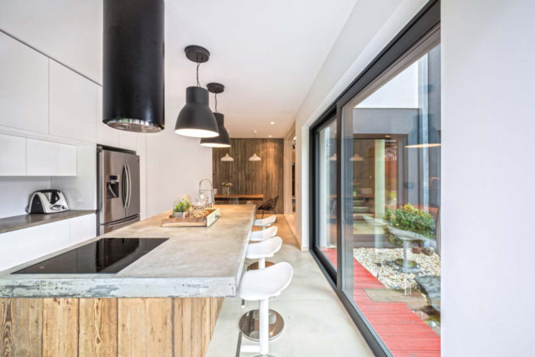 The kitchen is modern, with a rough wood and concrete kitchen island and modern hanging lamps