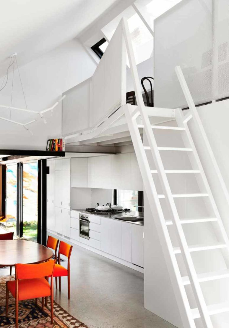 There's a staircase that leads to a small working space above the kitchen
