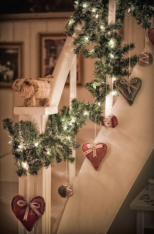 cute fir garland with lights and sewn hearts hanging