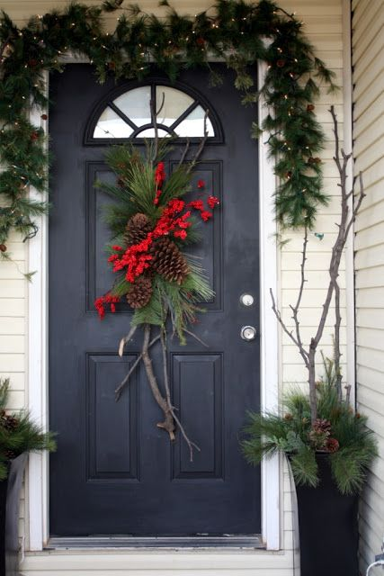 evergreen garland with lights, door decor with pinecones and branches in urns