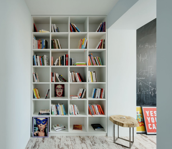 A large floor to ceiling bookshelf is placed between two areas, so it doesn't take necessary floor space in the two main zones
