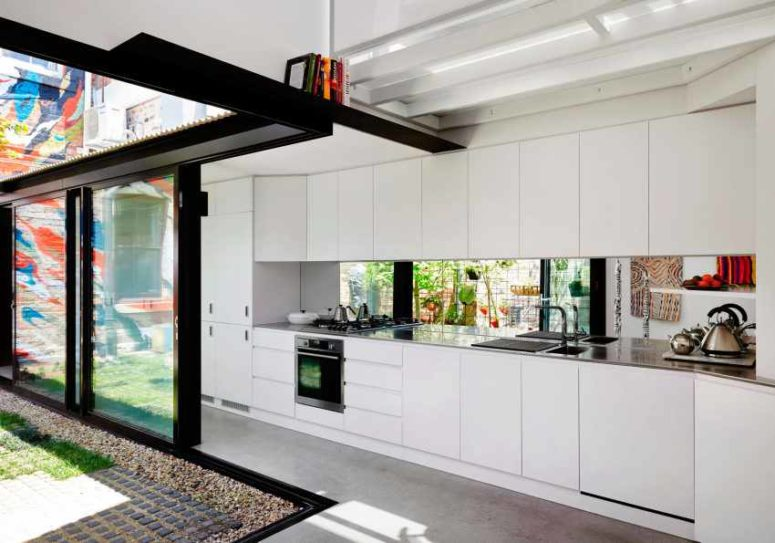 A mirror backsplash reflects the lights and makes the kitchen look more modern