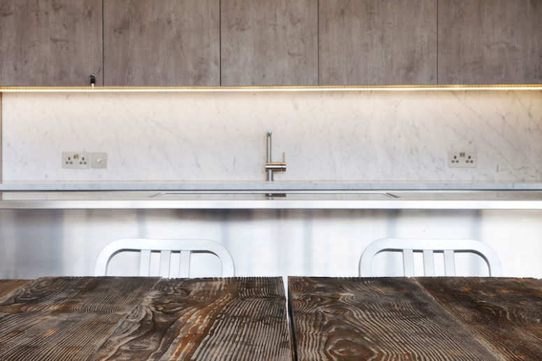 In the kitchen, white marble is combined with natural wood