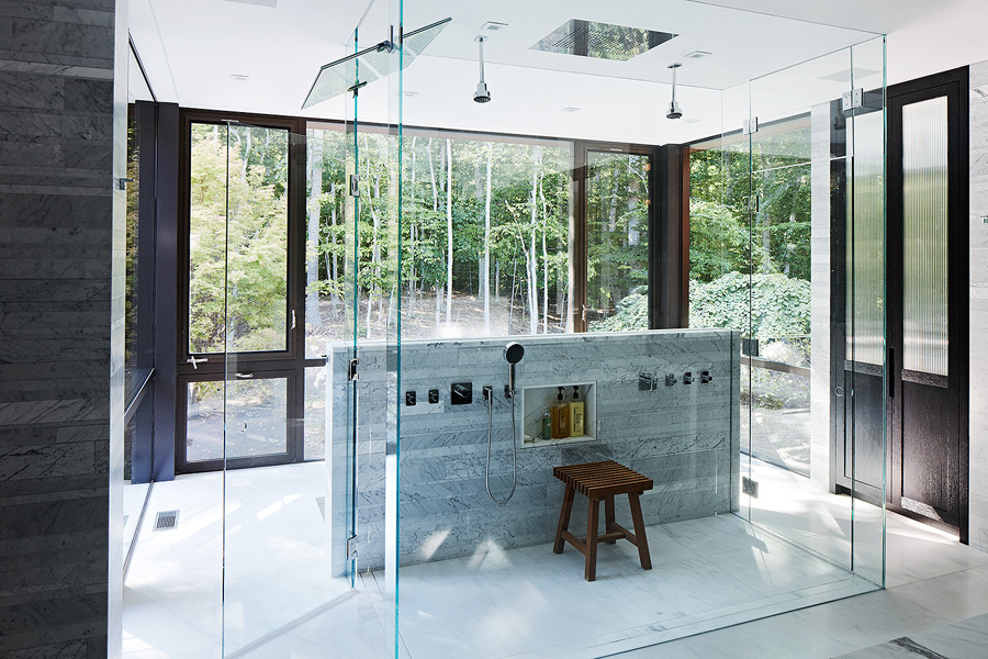 The bathroom features a glass cube shower and extensive glazing to catch all the best of the views