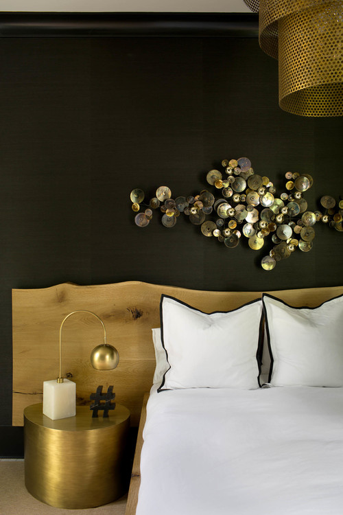 The focal point of the bedroom is a metallic wall art and its black and gold combo is refined