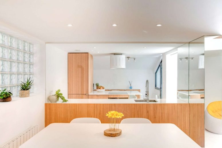 The kitchen is light-filled, with warm and light wood cabinetry that keeps the look modern yet inviting and cozy