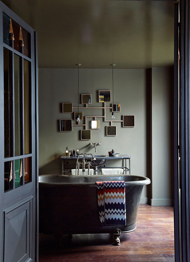 The master bathroom strikes with a mirror installation and a worn vintage bathtub and countertop