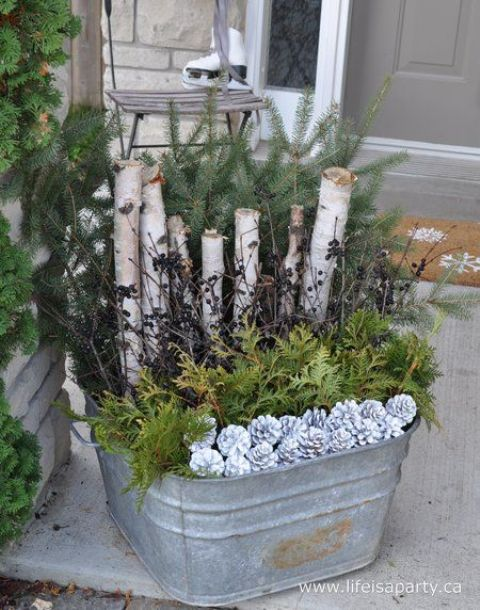 a galvanized bath with evergreens, branches, and snowt pincones