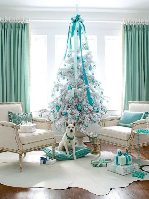 a white Christmas tree with tiffany blue ornaments and a large bow