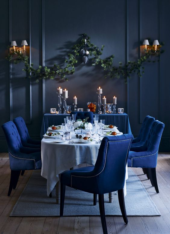 rich colours, moody lighting and shimmering surfaces with dark blue upholstery
