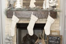 06 rustic mantel with pinecones and wood logs, white stockings and a barnwood sign to refresh the look