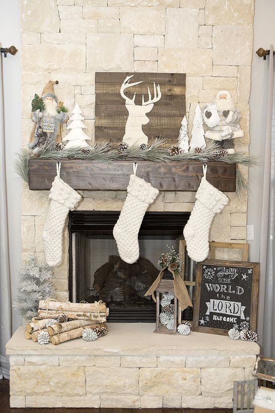 rustic mantel with pinecones and wood logs, white stockings and a barnwood sign to refresh the look