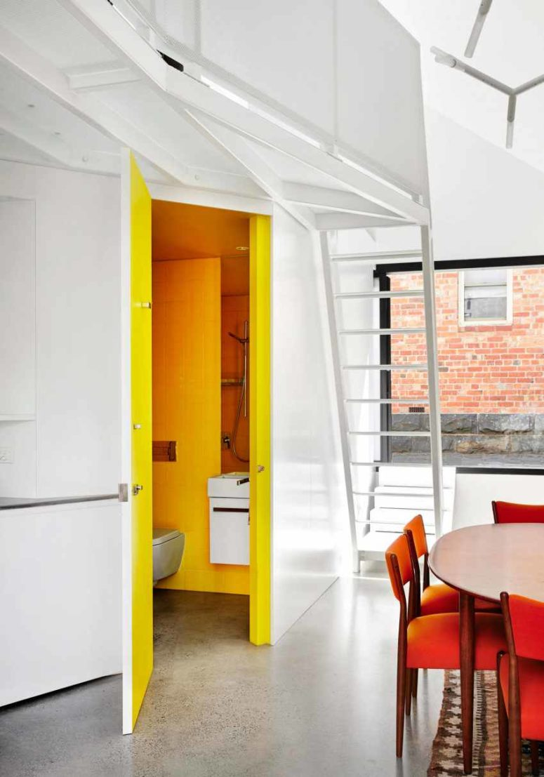 A sunny yellow bathroom is hiding behind one of the kitchen panels