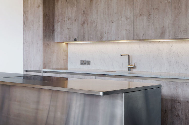 The brushed stainless steel island counter adds a modern touch to the decor