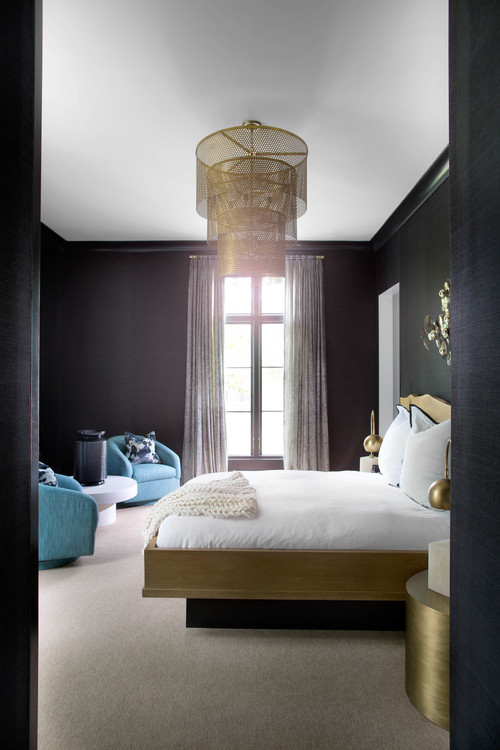 The dark bedroom is balanced with light blue chairs and a white coffee table