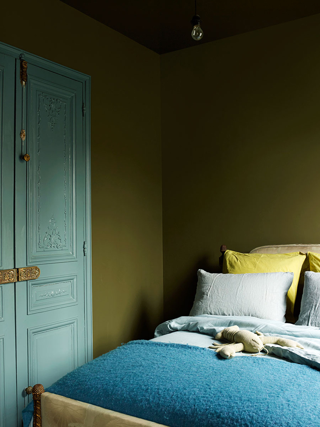 The guest bedroom is decorated in the same moody shade of green as the living room, and there are blue touches added