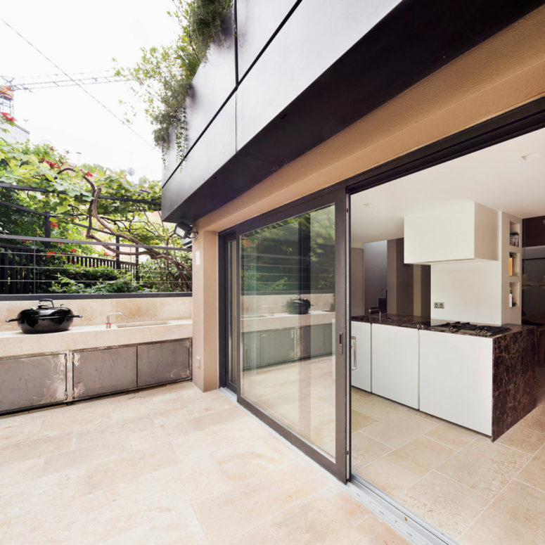The kitchen has a glass door that can be opened to the outdoor terrace to enjoy the fresh air