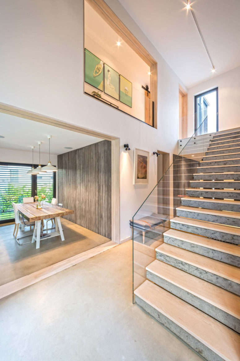 The staircase is made of concrete and glass railing for a stylish modern look