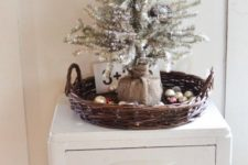 07 a silver tree wrapped with burlap, placed into a basket with ornaments