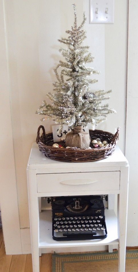 a silver tree wrapped with burlap, placed into a basket with ornaments
