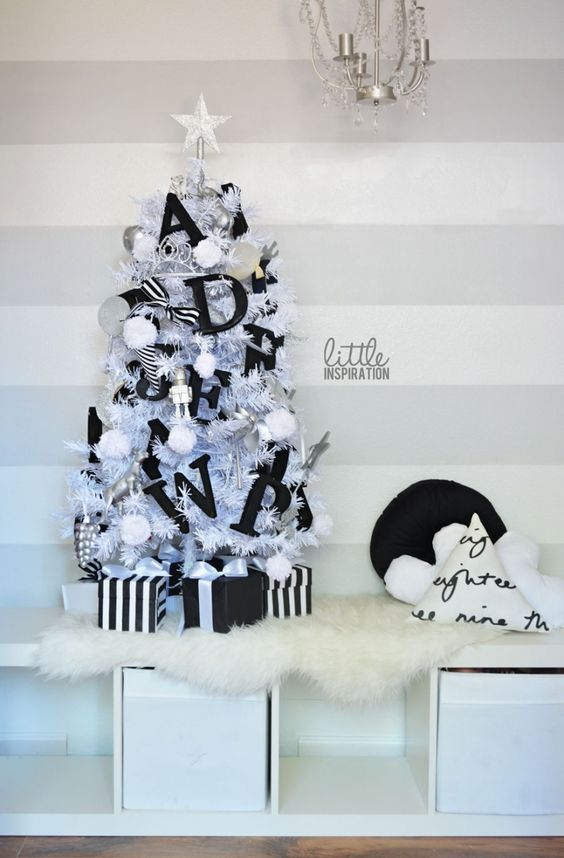a small christmas tree with black letter decor and pompoms