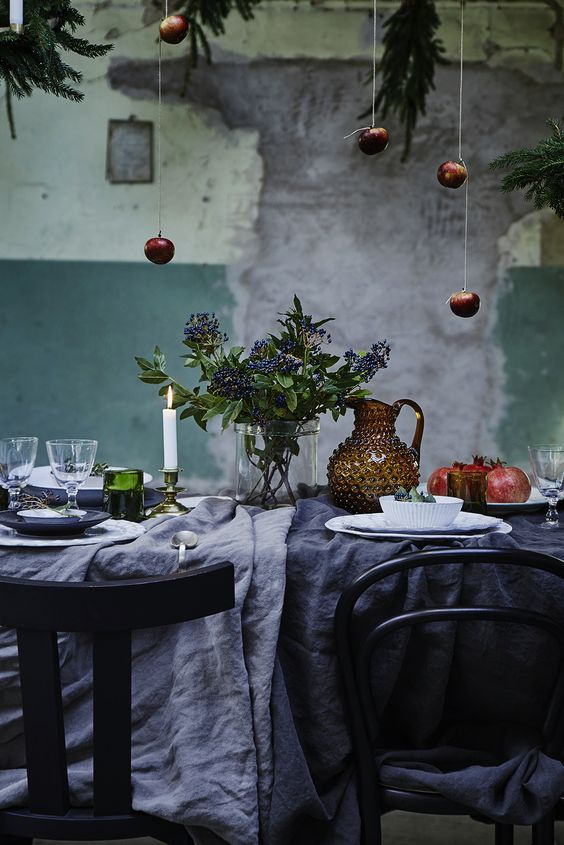 rustic table setting with dark textiles and hanging apples
