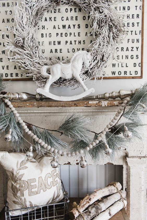 shabby chic mantel in off-white, a snowy wreath, garland and logs