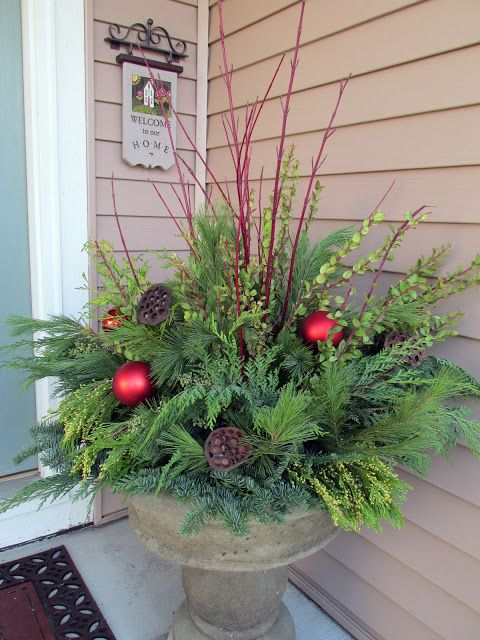 winter container with fresh evergreens, red branches and ornaments