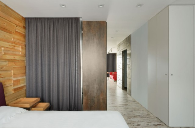The bedroom features an accent headboard wall made of wood pieces
