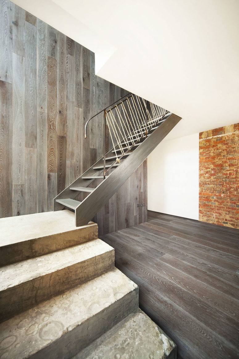 The wood-clad accent wall allows the staircase to blend in more easily