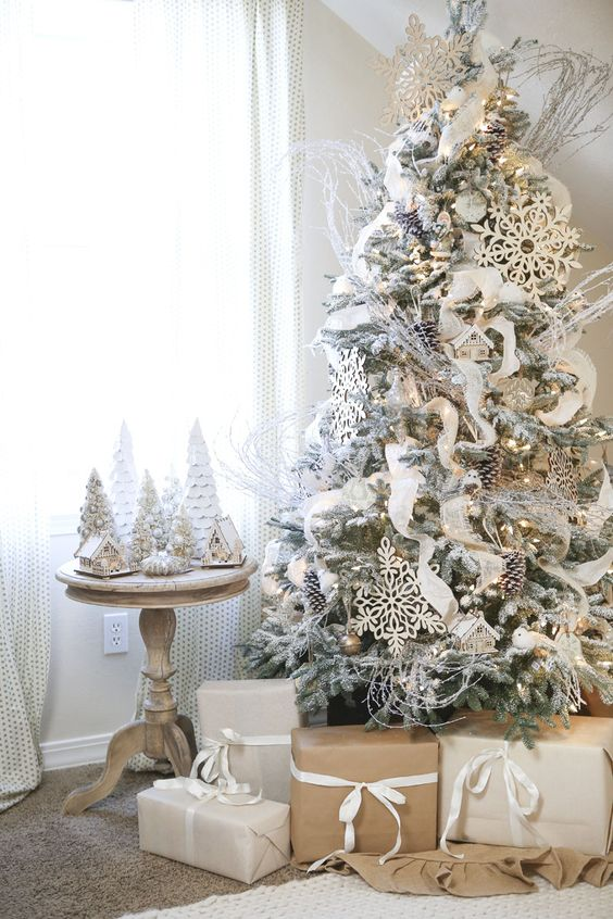 a flocked tree decorated in white and gold, with large snowflakes and snowy pinecones