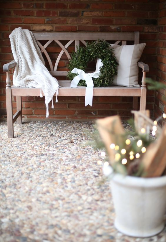 an elegant bench, a wreath with a white bow and some lights for simple decor