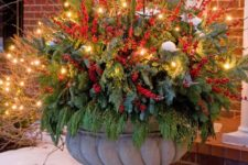 08 oversized urn with evergreens, faux berries and red branches is glowing up thanks to the lights