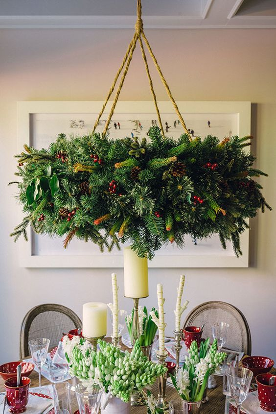 oversized evergreen wreath chandelier with pinecones and berries