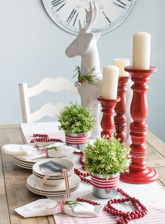 red and white tablescape with candles, fresh greenery and cranberries