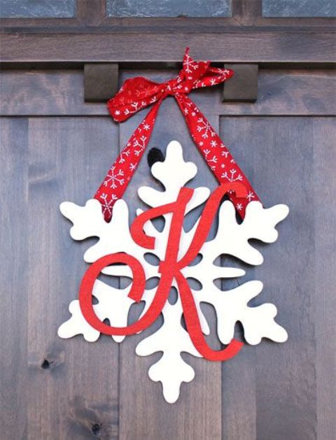 snowflake door hanger with a monogram and red ribbon