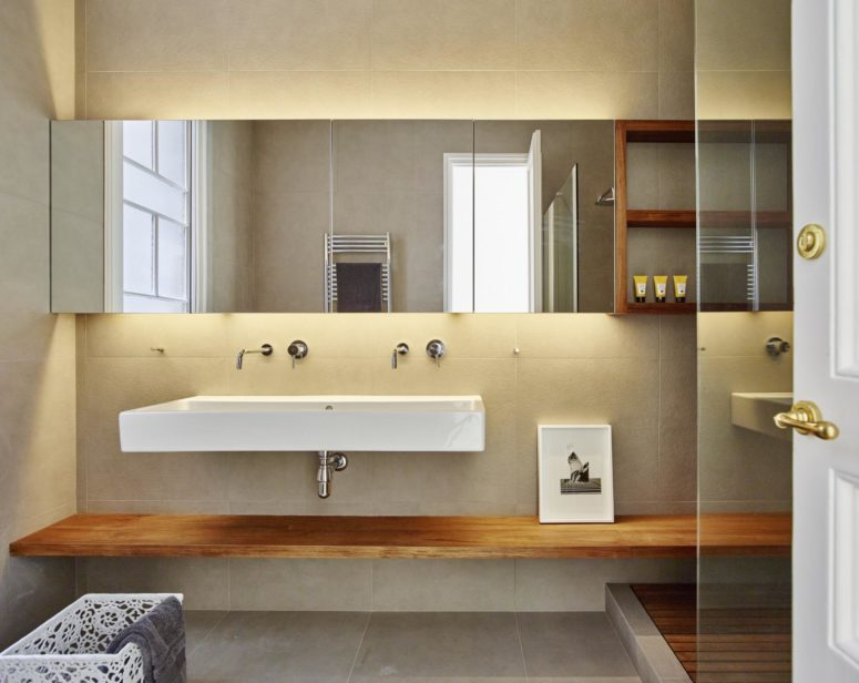 The bedroom is modern and functional, with a large mirror and a walk-in shower