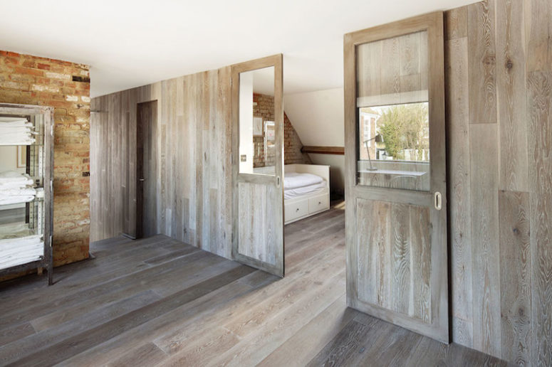 The bedrooms are separated by wooden partitions that match the floor