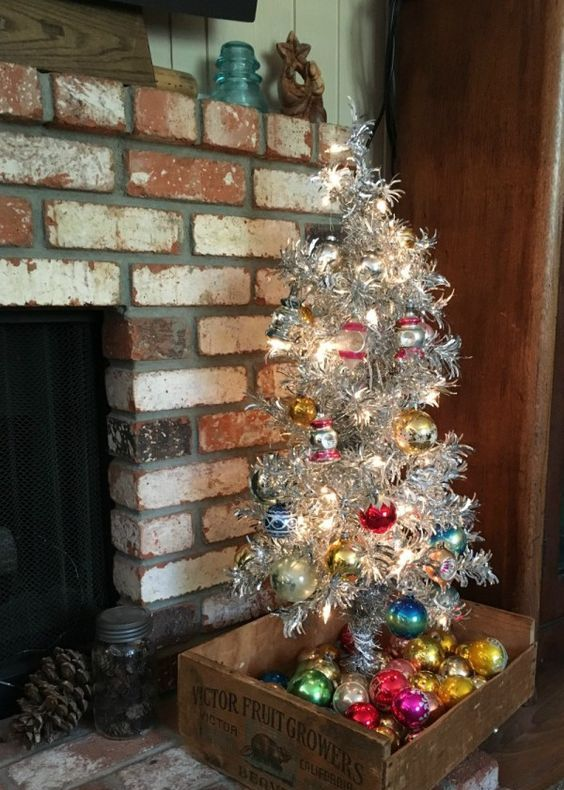 aluminum Christmas tree with bold vintage ornaments and ornaments displayed in the crate