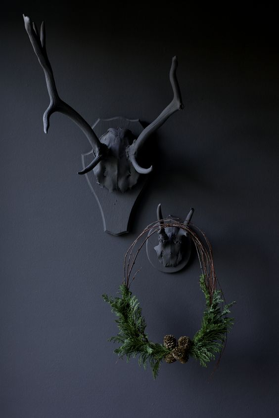 black antlers and a small twig wreath with evergreens and pinecones