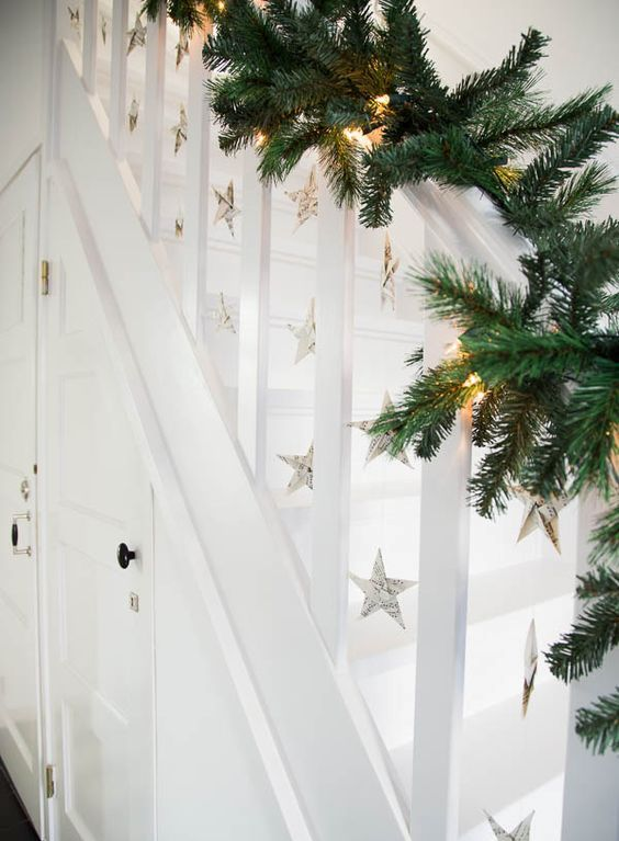 evergreen garland with lights and paper stars hanging