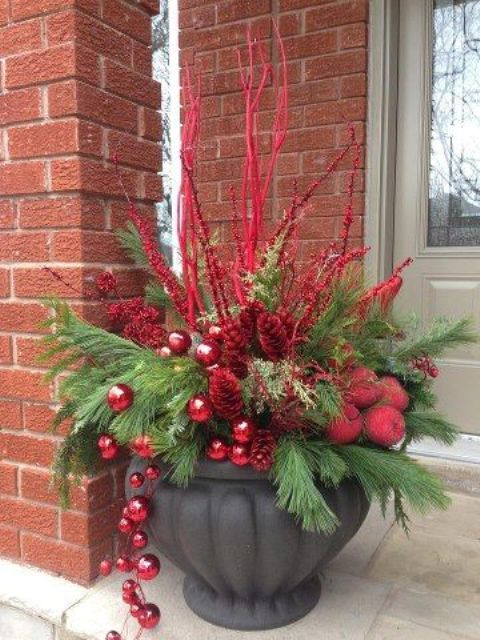 outdoor arrangement with a large urn, evergreens, red branches and ornaments is perfect for a welcoming Christmas porch decor