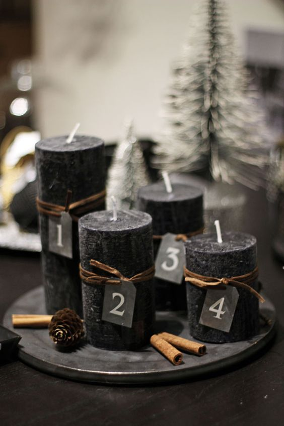 black candles on a dish, cinnamon sticks and pinecones