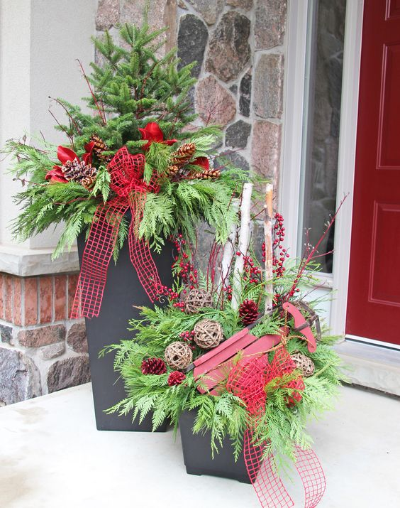 containers with evergreens, vine spheres and red ribbon